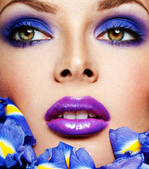 beautiful woman face with professional makeup, surrounded by blu