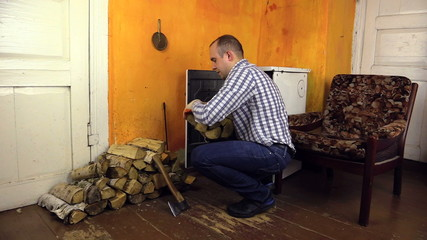 man handles wood in pile near old stove in living rural room