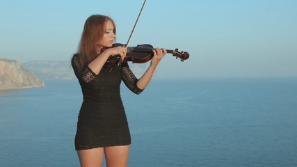Young violinist plays with inspiration by the sea