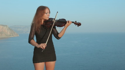 Emotional violinist playing while standing on сrimean mountain