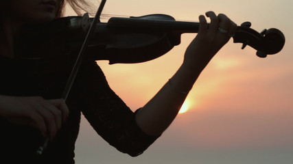 Beautiful girl playing the violin while the sun sets in the sea