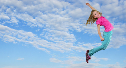 little girl jumping and dancing against blue cloudy sky