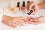 Beautiful girl manicurist doing manicure for woman poster