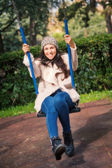 Portait of young woman swinging outdoors in a park in autumn.
