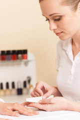 Close-up Of Beautician Hand Filing Nails Of Woman In Salon.