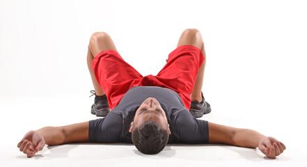 Atleta deportista agotado recostado en el piso.