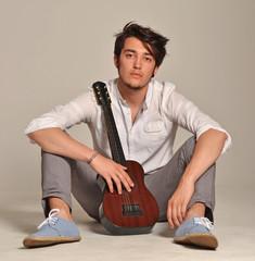 Joven de la calle sujetando una guitarra.
