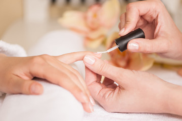 Woman in nail salon receiving manicure by beautician.