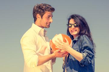 Couple having fun with a beach ball