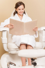 Young woman receiving pedicure in hairdressing salon.