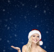 Young girl in Christmas cap gestures palm up, on blue background