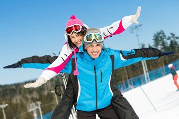 Half-length portrait of happy couple of alps skiers have fun