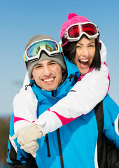 Portrait of happy couple of skiers have fun