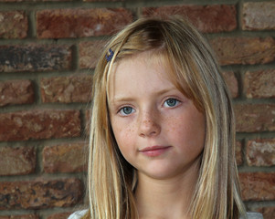 A young girl looking pensive, with a brick wall background