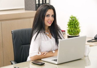 Young pretty business woman working on laptop in office