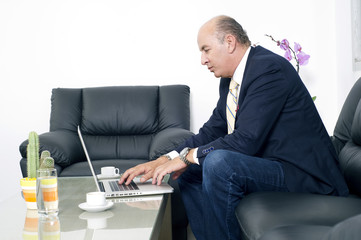 Senior Businessman working on laptop in his office