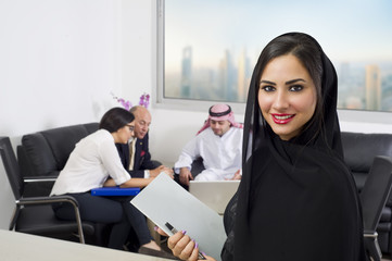 Arabian Businesswoman & Employees meeting in the background