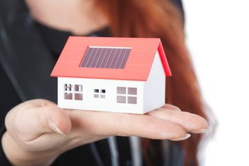business woman with close up of mini solar house