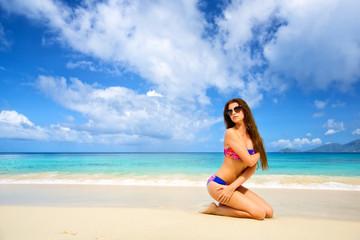 Beautiful young female in bikini on tropical beach