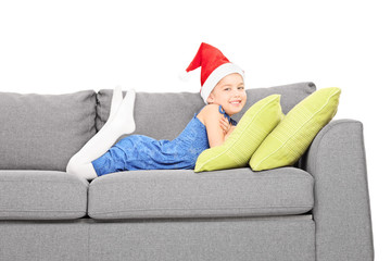 Cute girl with Santa hat lying on a couch