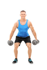 Young athlete exercising with two barbells