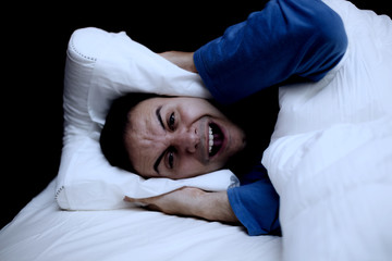 Man using a pillow to cover his ears