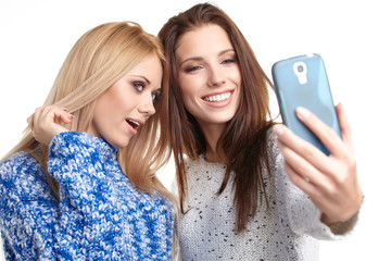 two beautiful girls making selfies at studio