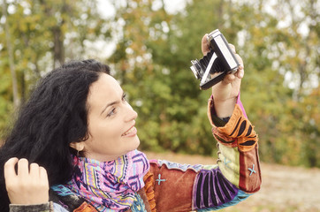 Brunette woman with film photo camera, self photography