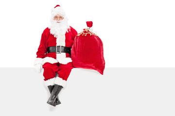Santa holding a bag of presents seated on a panel