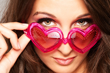 Young smiling girl with heart-shaped glasses