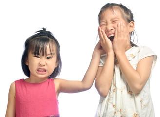 Siblings teasing, asian little girl pulling her sister's ear