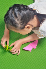 asian child makes origami paper craft
