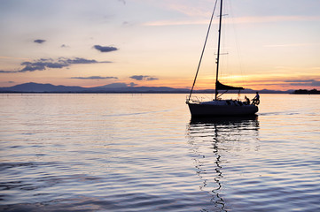 Barca a vela sul lago al tramonto