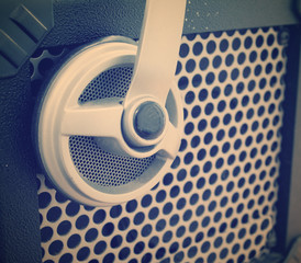 close up of a guitar amplifier grill with a headset on it