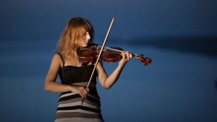 Talented girl playing the violin standing on a cliff next to the