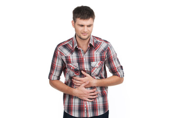 Young man with strong stomach pain isolated on white background.