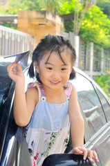 asian little child holding a paper plane in the car