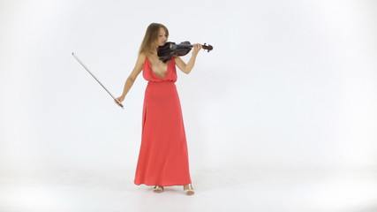 Young violinist plays in a long dress on her a musical