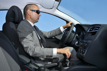young man in suit driving a car