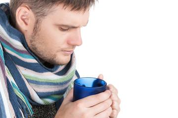 Portrait of sick man holding cup of tea.