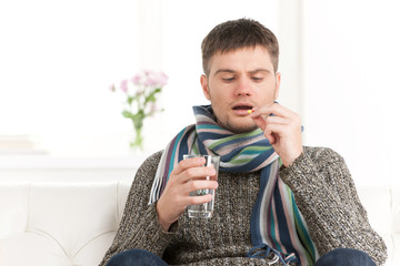 Sick caucasian man holding pills and water.