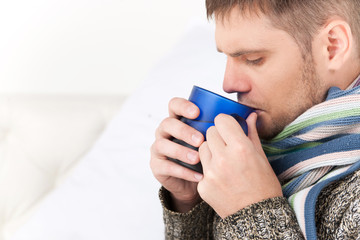 closeup on man on sofa drinking hot tea