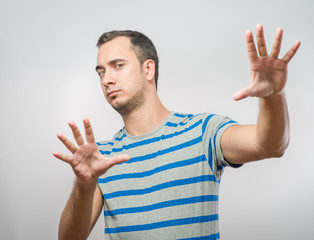 frightened man defends himself with his hands