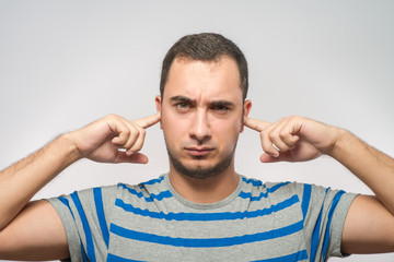stressed man covering his ears