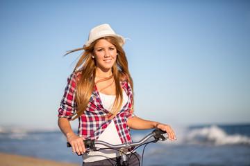 girl sitting on bike to the beach