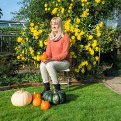 Frau sitzt im Garten mit Kürbissen