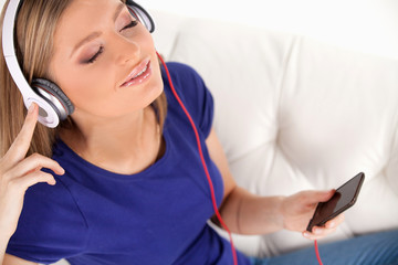 beautiful young girl listens to music on headphones.