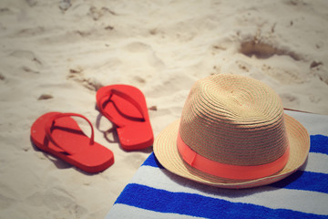 Straw hat, towel and flip flops on tropical beach