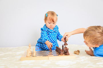 little daughter playing chess with brother