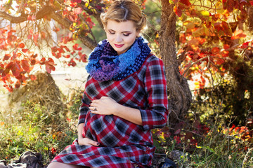Pregnant girl is wearing checkered dress in park